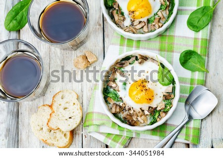 spinach, mushrooms baked egg on a white wood background. toning. selective Focus - stock photo