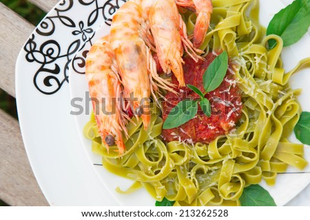 Spinach pasta with shrimps and tomato sauce.Close up - stock photo