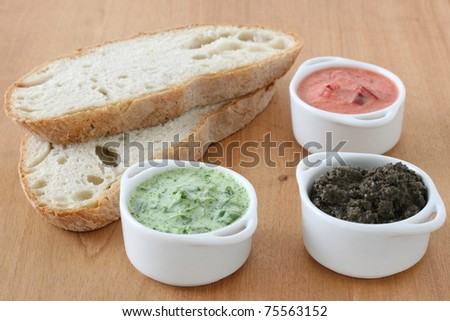spinach, pepper and olive dips in small bowls with bread - stock photo