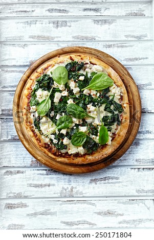 Spinach pizza with goat cheese - stock photo