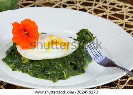 Spinach,  poached egg and edible flower of water cress - stock photo