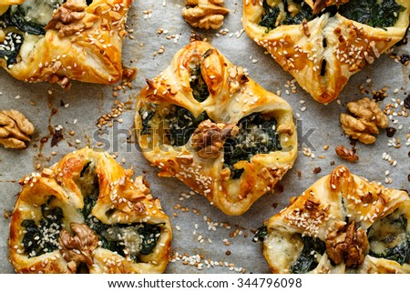 Spinach puffs with addition of Gorgonzola cheese, walnuts and sesame seeds - stock photo