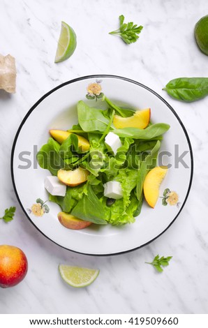 Spinach salad with fruit on marble. Spinach veggies salad . Organic spinach salad. Green spinach salad. Spinach salad with ingredients - stock photo