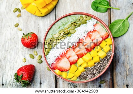 Spinach smoothie bowl with strawberries, coconut, mango, pumpkin seeds and seeds Chia. toning. selective focus - stock photo