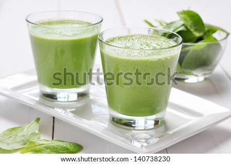 Spinach smoothies in glass on a wooden background - stock photo