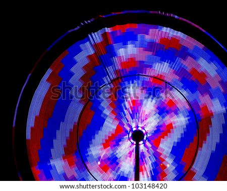 Spinning amusement park rides at Panama City Beach, Florida, with motion blur - stock photo