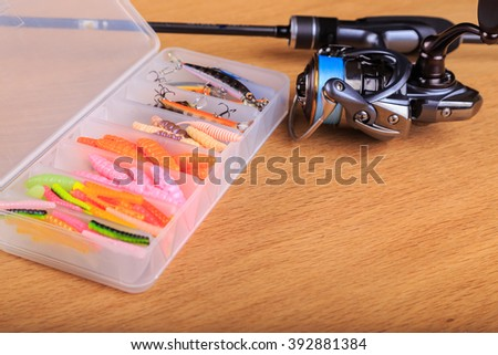 Spinning bait on the table. Reel and jig baits - stock photo