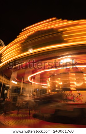 Spinning carousel at night, motion blur - stock photo