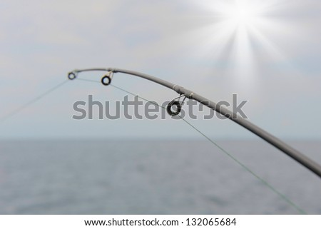 Spinning close-up in the hands of a fisherman at sea - stock photo