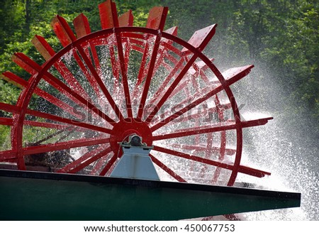 spinning red paddle wheel on vintage river boat with spraying water droplets