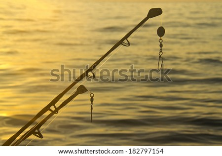 spinning rods in front of sea water - stock photo