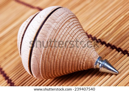 Spinning top on wood backround - stock photo