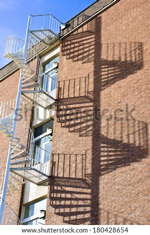 Spiral fire escape staircase on a building with dramatic shadows