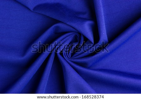 Spiral folds on blue cloth. High resolution texture - stock photo