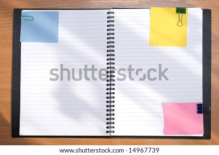 spiral notebook and empty notes over wooden table - stock photo