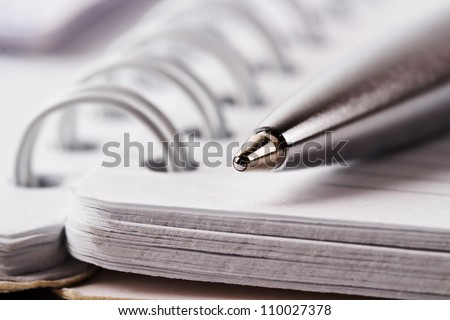 Spiral notebook and pen - stock photo