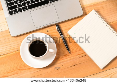 Spiral Notebook, pen and cup of coffee on laptop keyboard  - stock photo