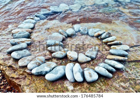 Spiral of white pebbles on the sea boulder - stock photo