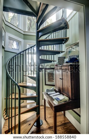 spiral staircase in home with lots of windows - stock photo
