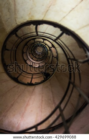 Spiral Stairs. Arch of Triumph, Paris (France): view of the internal stairway from the ground floor. Art of image from center of stair. Selective focus - stock photo