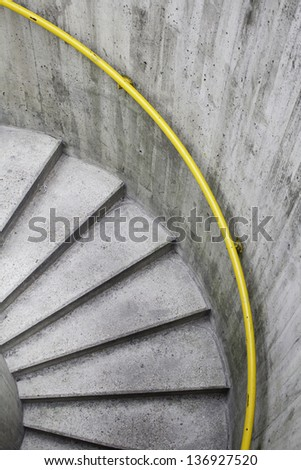 Spiral stairs with yellow railing inside a warehouse - stock photo