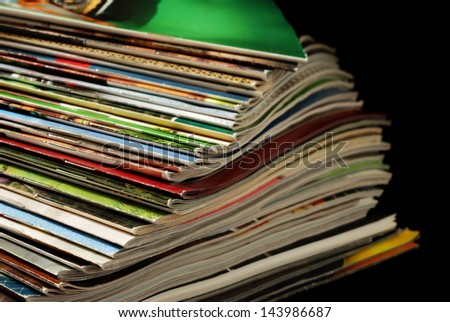 Spiraled stack of colorful magazines and mail order catalogs (with slightly worn edges) on black background with copy space.  Macro with shallow dof.