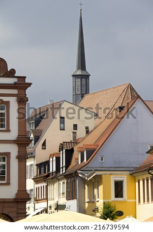 Spire of a small church rises above the historical houses of Speyer, Germany - stock photo