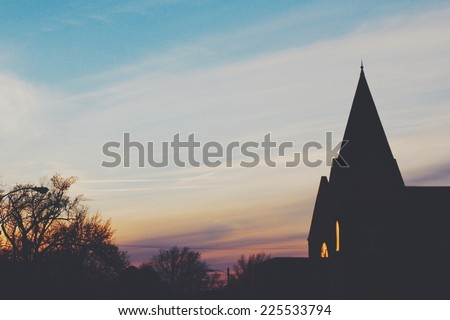 Spires of a church in silhouettes with lights coming through the windows. - stock photo