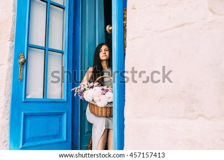 Spirit of Provence in an old town. Beautiful young girl in grey dress with basket full of summer flowers sitting on the chair next to opened blue doors.
