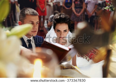 Spiritual beautiful bride and groom taking vows in church at Bible - stock photo