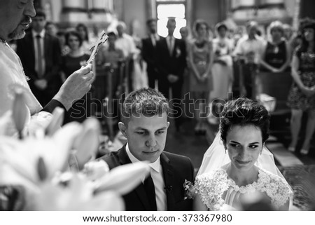 Spiritual beautiful bride and groom taking vows in church at Bible b&w - stock photo