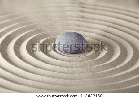 spirituality and purity stone in sand circles spa background in zen garden concept for relaxation concentration and meditation - stock photo