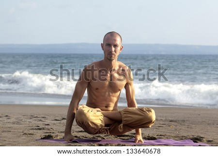 Spirituality man sits lotus pose yoga and rises up by hands - stock photo