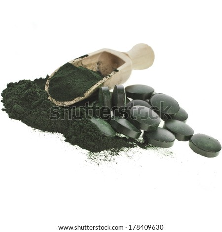 Spirulina algae  powder and tablets in spoon scoop , isolated on white background  - stock photo