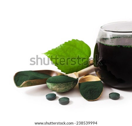 Spirulina algae powder in wooden spoons and cup isolated on white background  - stock photo