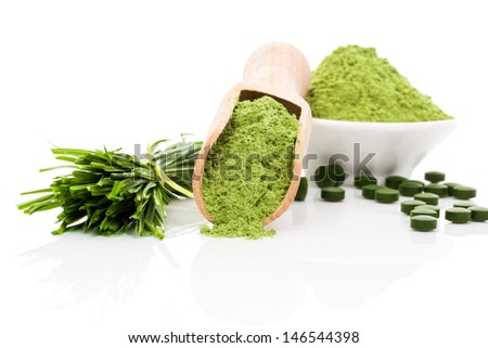 Spirulina; chlorella and wheatgrass. Green food supplement. Green pills; wheatgrass blades and ground powder isolated on white background. Healthy lifestyle. - stock photo
