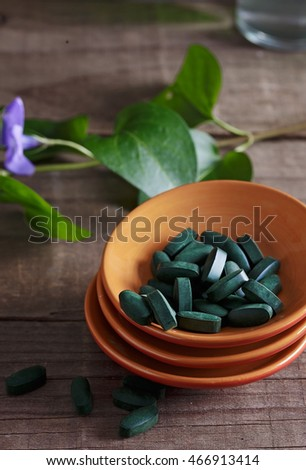 Spirulina pills in a ceramic plate over wooden rustic background