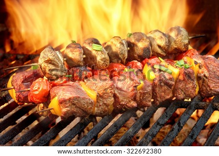 Spit Roast Beef Kebabs On The Hot Flaming BBQ Grill Close-up - stock photo