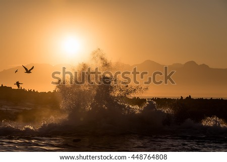 Splash at Seal Island A wave crashes during sunrise at the shores of Seal Island, False Bay, South Africa  - stock photo