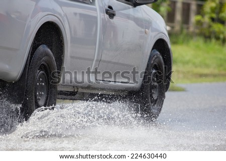 Splash by a car as it goes through flood water - stock photo