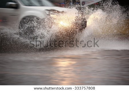 Splash by a car through flood water after hard rain,blurry movement  and selective focus.