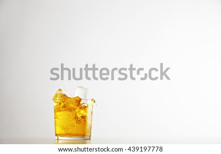 Splash cocktail drink inside transparent glass with ice cubes isolated on white, commercial