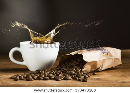 Splash coffee in cup and saucer on a wooden table. Dark background. - stock photo