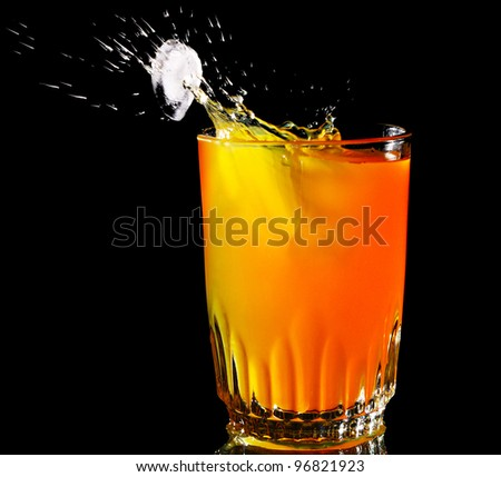 Splash glass of fresh orange juice with ice on a black background