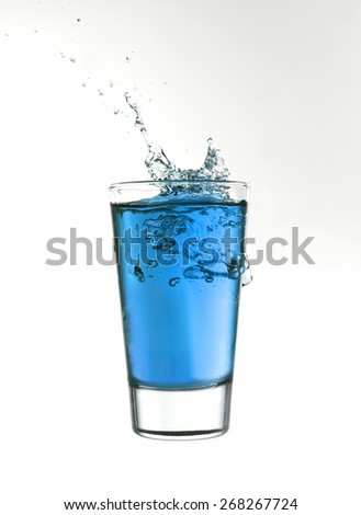 Splash in a glass of blue lemonade isolated on white background - stock photo