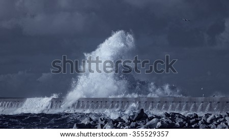 Splash of a big stormy ocean wave against a pier from the north of Portugal. Used infrared filter. Toned blue.