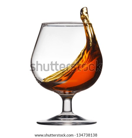 Splash of cognac in glass on white background - stock photo