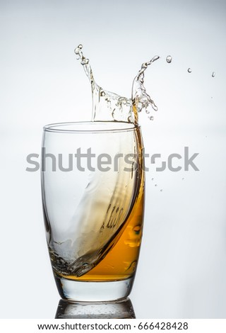 splash of drink from a glass with reflection