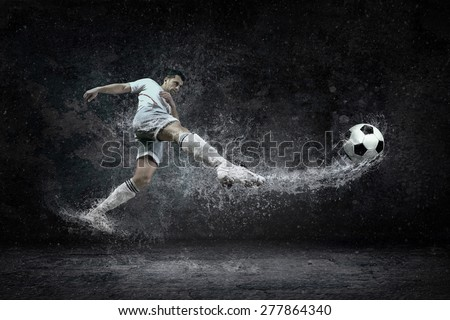 Splash of drops around football player under water - stock photo