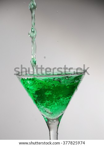 Splash of green liquid (cocktail, juice) pouring into the martini glass. Object on a white background. - stock photo